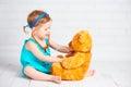 Girl playing doctor and treats teddy bear