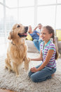 Girl playing with dog while parents relaxing at home Royalty Free Stock Photo