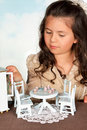 Girl playing with doll's furniture Royalty Free Stock Photography