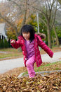 Girl playing in fall leaves Stock Photo