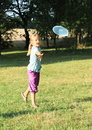 Girl playing frisbee little on meadow Royalty Free Stock Image