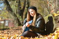 Girl playing the guitar in autumn park Royalty Free Stock Image