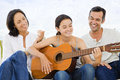 Girl playing guitar with her parents middle aged Stock Photo