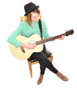 Girl playing guitar teen musician sitting cross legged on a chair acoustic from above Stock Photo