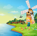 A girl playing with her birds near the barnhouse with windmill illustration of Stock Image