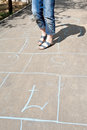 Girl playing in hopscotch on urban alley sunny day Stock Images