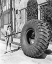 Girl playing with a huge tire and stick Royalty Free Stock Photo