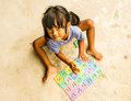 Girl playing jigsaw on the cement ground Royalty Free Stock Photo