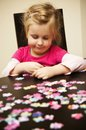 Girl playing with jigsaw puzzle a cute young four year old while sitting at table at home Royalty Free Stock Photo