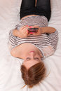 Girl playing with mobile phone young pretty her on a bed Royalty Free Stock Photos