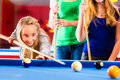 Girl playing pool billiard with family together brother kick off queue and balls on table Stock Photos