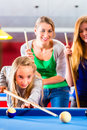 Girl playing pool billiard with family together brother kick off queue and balls on table Stock Images