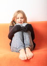 Girl playing with pullover tied kid little on orange cover Royalty Free Stock Photos
