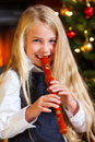 Girl playing recorder on christmas eve Stock Photo