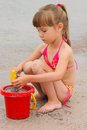 Girl playing with sand on the sea shore Royalty Free Stock Photo