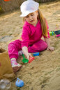 Girl playing in sandbox a cute four year old with colorful toys Royalty Free Stock Photo