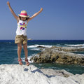 Girl playing by sea young jumping on rocks with blue and sky background Stock Image