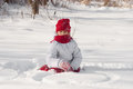 Girl playing in the snow little a red hat Stock Photos