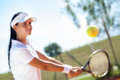 Girl playing tennis young hitting ball Stock Photos