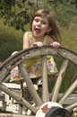 Girl playing with wagon wheel Stock Images