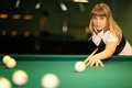 Girl plays billiards in a club Royalty Free Stock Photography