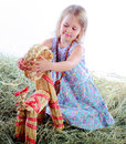 The girl plays in hay plays with a wattled goat Royalty Free Stock Photography