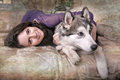 Girl plays with malamute teen at home Stock Images