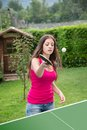 Girl plays ping pong young brunette table tennis outdoors Royalty Free Stock Photography