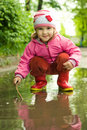 Girl plays in the puddle Royalty Free Stock Photos