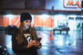 Girl pointing finger on screen smartphone on background illumination bokeh color light in night atmospheric city Royalty Free Stock Photo