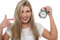 Girl pointing towards old fashioned time piece Royalty Free Stock Images
