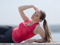 Girl with ponytail poses outdoors young woman arm raised lying on side looking at camera Royalty Free Stock Photography