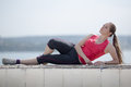 Girl with ponytail poses outdoors young woman in sportswear lying on side looking up Stock Photo