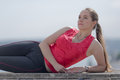 Girl with ponytail poses outdoors young woman in sportswear lying on side looking up Royalty Free Stock Photo