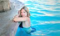 Girl in the pool a bathing suit floating Stock Photos