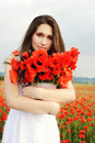 Girl with poppies beautiful young woman staying in field of flowers Stock Photos