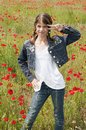 Girl with poppies dance style on the meadow posing lots of red around her Royalty Free Stock Photography