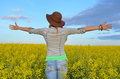 Girl posing in a field of yellow flowers with hat Stock Photos