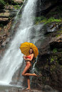 Girl posing in front of waterfalls with yellow umbrella Stock Image