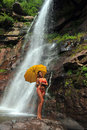 Girl posing in front of waterfalls with yellow umbrella Royalty Free Stock Images