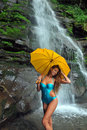 Girl posing in front of waterfalls with yellow umbrella Stock Photography