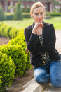 Girl posing in the park young blond beautiful black jacket a spring Stock Image