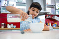 Girl pouring milk in breakfast bowl Royalty Free Stock Photo