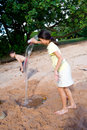 Girl pouring water into a dug out hole in the sand Royalty Free Stock Photos