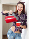 Girl pours water into a cup the from the kettle Stock Images