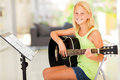 Girl practicing guitar cheerful preteen at home Royalty Free Stock Photos