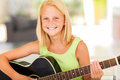 Girl practicing guitar happy pre teen at home Stock Images