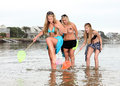 Girl pranks her friend four girls are walking in the water and the one blonde into thinking a crab got hold of toes some of the Stock Photo
