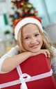 Girl with present portrait of cheerful red giftbox looking at camera on christmas evening Royalty Free Stock Image