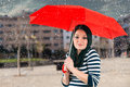 Girl is protected from bad weather young with a red umbrella Royalty Free Stock Image